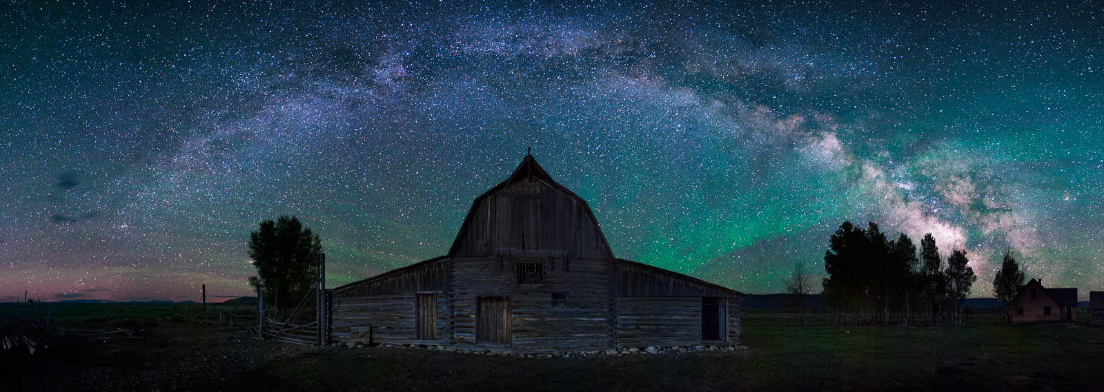 The milky way arcs over the North Moulton Barn in Grand Teton National Park with airglow burning brightly in the sky