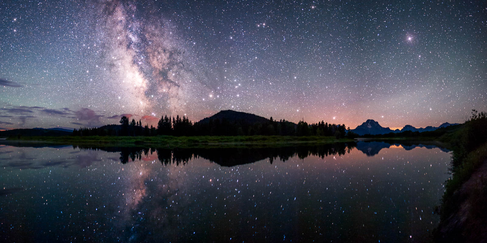 The milky way reflects in the Snake River at the famous Oxbow Bend in Grand Teton National Park